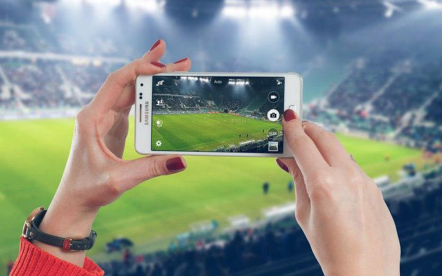 Woman taking picture of football stadium