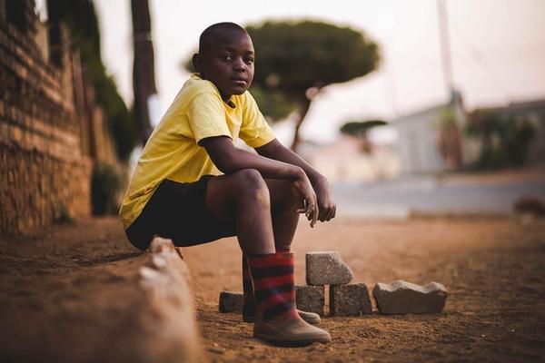boy sat on street wearing yellow shirt and black shorts