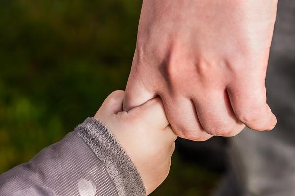 Close up of child and parent linked hand in hand