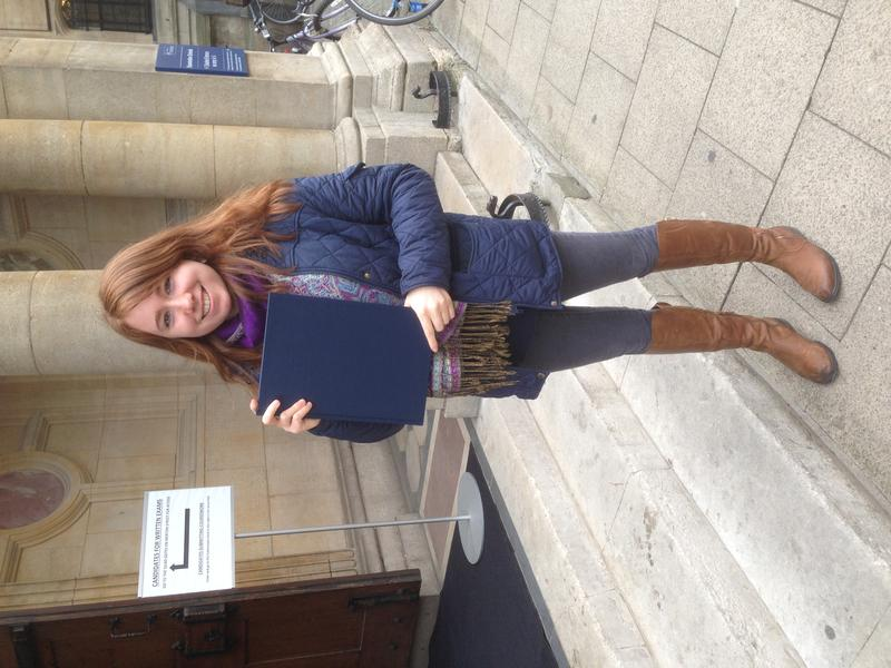Rhaina Cohen holding her MPhil thesis