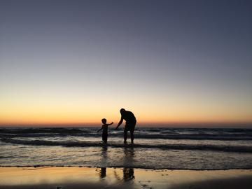 Child playing with guardian in sea