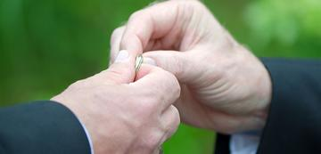 men holding a wedding ring