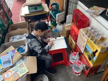 Chinese child does homework inbetween boxes of store supplies