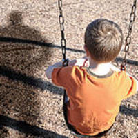 Child sits alone on a swing, a shadow of a man hovers over him