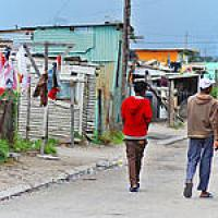 Men walking on street with huts