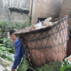 Chinese man carries basket on his back